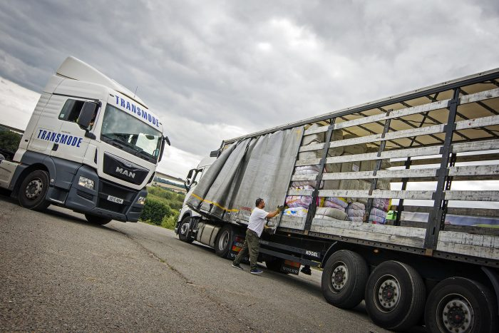 A HGV driver next to a lorry belonging to Transmode, a company that prioritises the health and wellbeing of its drivers.